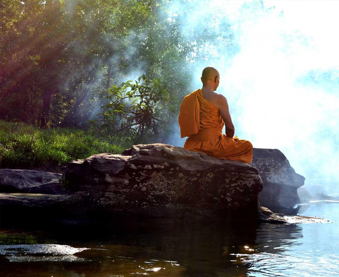 נזיר בודהיסטי יושב על סלע מעל נהר ועושה מדיטציה בדך הזן
